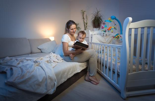 赤ちゃんのベビーベッドに座って本を読んでいる若い母親