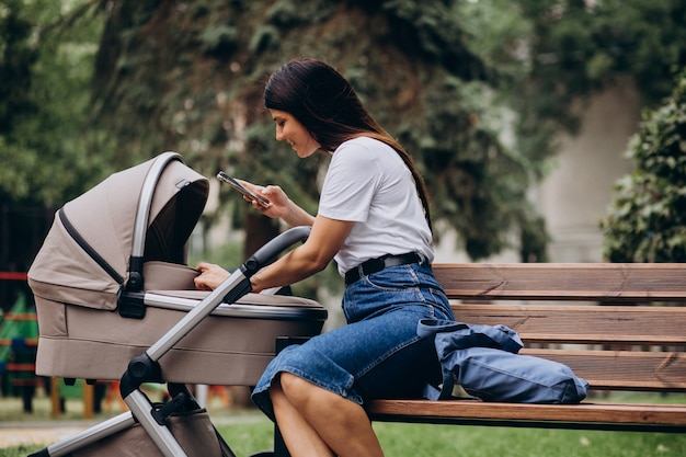Young mother sitting on bench in park with baby stroller