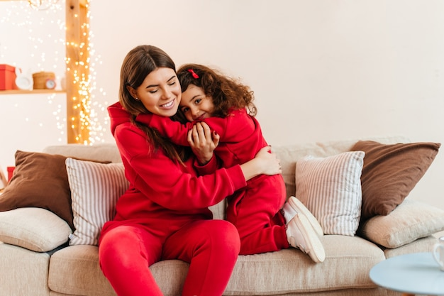 Young mother sitting on couch woth preteen girl. indoor shot of mom and daughter in red clothes embracing on sofa.