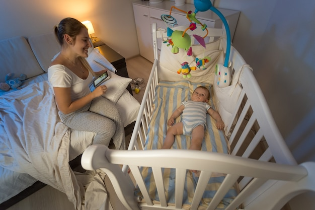 아기 침대 옆에 앉아 아기를 바라보는 젊은 엄마