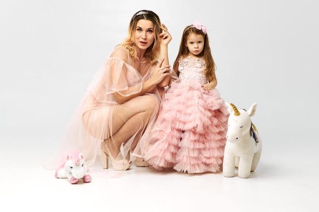 床に座っている若い母親とかわいい魅力的な小さな娘の両方が派手なピンクがかった服を着て、おもちゃで遊んでいます