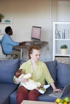 Молодая мать сидит на диване, убаюкивая ребенка, используя портативный компьютер дома