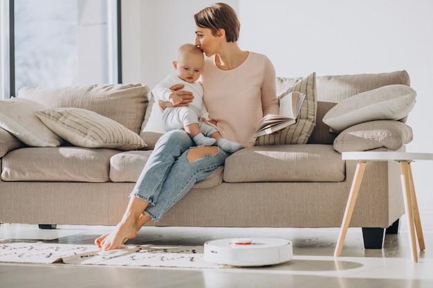 幼児の息子と一緒にソファに座り、ロボット掃除機が家事をしているのを見ている若い母親