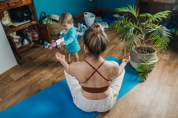 Молодая мать, сидящая на полу, наслаждается медитацией, занимается йогой дома со своей маленькой дочерью