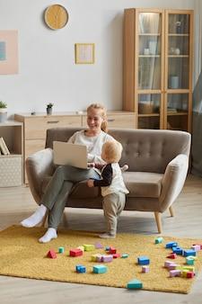 Молодая мать сидит на диване и использует ноутбук, а ее сын играет рядом с ней в гостиной