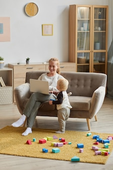 Young mother sitting on the sofa and using laptop with her son playing near her in the living room