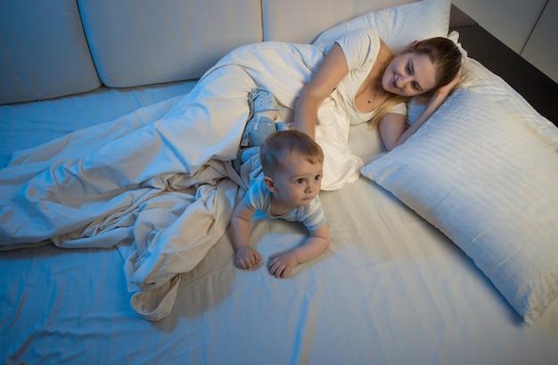 ベッドで彼女の男の子と一緒に寝ている若い母親