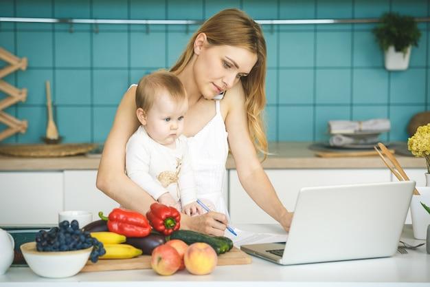若い母親は笑みを浮かべて、調理し、モダンなキッチンで彼女の赤ん坊の娘と遊ぶ。電話を使用して。在宅勤務。