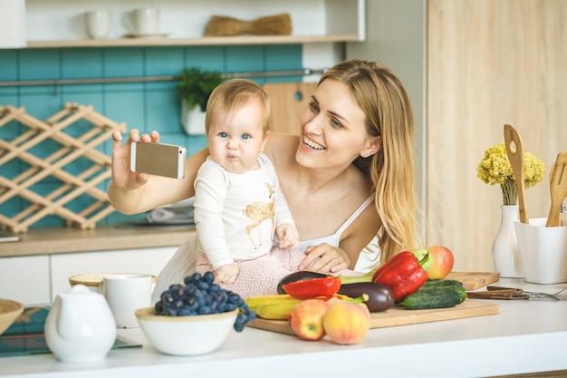 若い母親は笑みを浮かべて、調理し、モダンなキッチンで彼女の赤ん坊の娘と遊ぶ。在宅勤務。 selfieをやっている赤ちゃんを持つ女性。