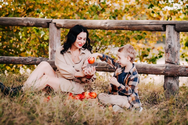 A young mother and son hold a small hedgehog and apples in their hands