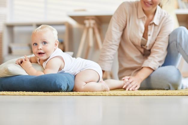 집에서 시간을 보내는 젊은 어머니는 그녀의 작은 아기 아들, 가로 샷 바닥에 휴식