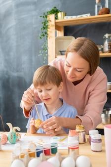 息子の後ろに立って、彼が卵にイースターのデザインを作るのを手伝っている若い母親