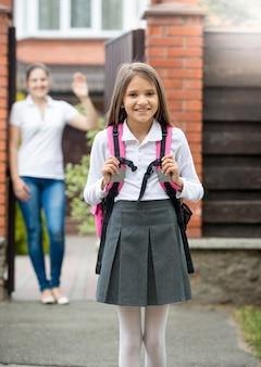 Молодая мать стоит в дверях и машет своей дочери, идущей в школу