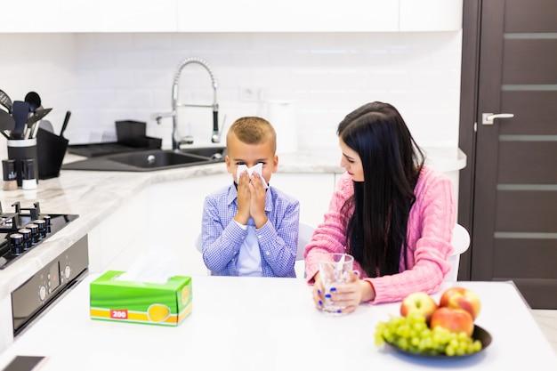 La giovane madre sta con suo figlio malato in cucina e dà trattamenti in cucina