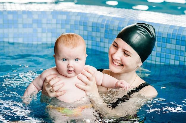 Молодая мать, инструктор по плаванию и счастливая маленькая девочка в детском бассейне.