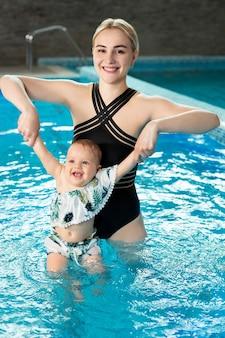 Молодая мать, инструктор по плаванию и счастливая маленькая девочка в бассейне. учит ребенка плавать.