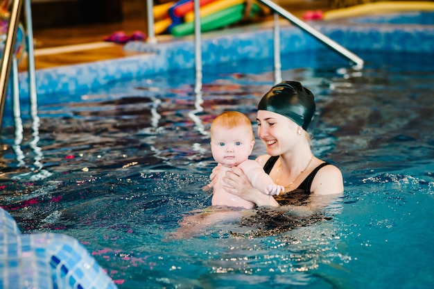 Young mother, swimming instructor and happy little girl in paddling pool. teaches infant child to swim. enjoy first day of swimming in water. mom holds hand child preparing for diving. doing exercises