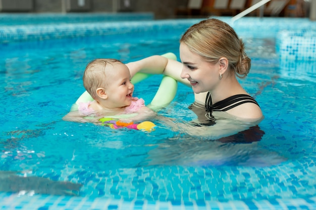 Young mother, swimming instructor and happy little girl in the pool. teaches infant child to swim.