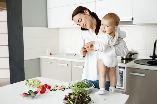 Young mother taking care of little child, talking on phone and cooking at same time