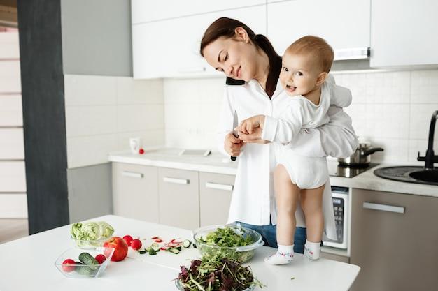 若い母親が小さな子供の世話をして、電話で話して、同時に料理