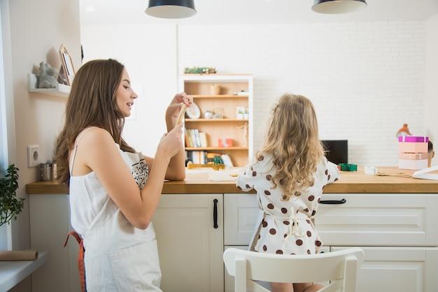 ジンジャーブレッドクッキーを飾る彼女の子供の写真を撮る若い母親。クリスマスの時期にキッチンでママと娘が一緒に