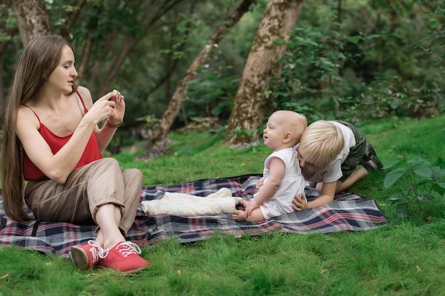 電話で彼女の子供たちの写真を撮る若い母親。家族みんなでピクニック。