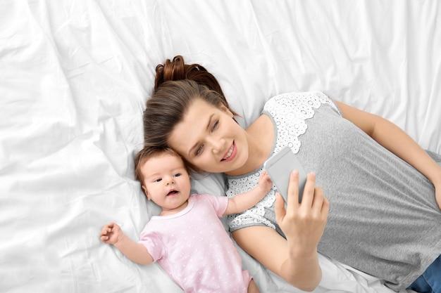 自宅のベッドで赤ちゃんと一緒に自分撮りをしている若い母親