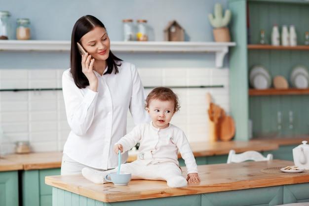 Молодая мама разговаривает по телефону у себя дома на кухне, наблюдая за ребенком