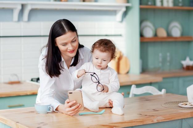 그녀의 팔에 아기와 함께 부엌에서 집에서 전화로 이야기하는 젊은 어머니