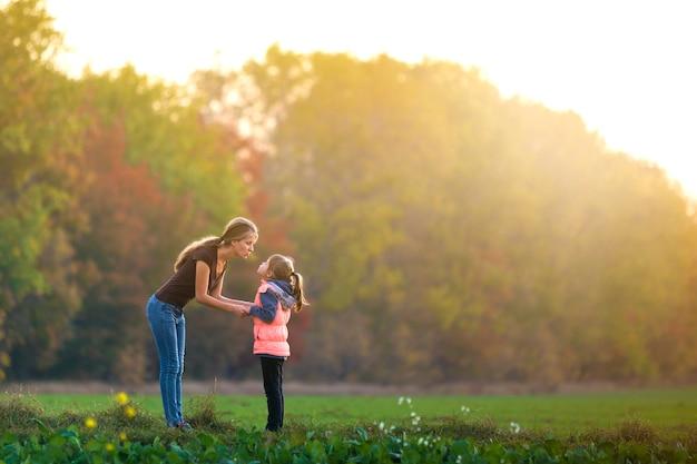 Молодая мать разговаривает с ребенком девочка, стоя на зеленом лугу, держась за руки