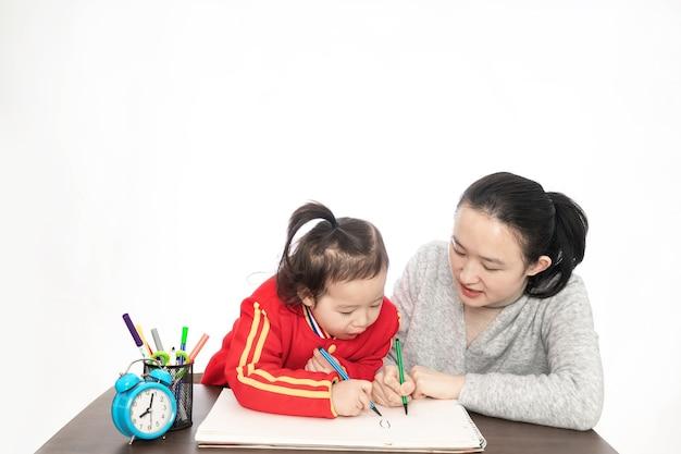 젊은 어머니는 페인트를 딸을 가르치고