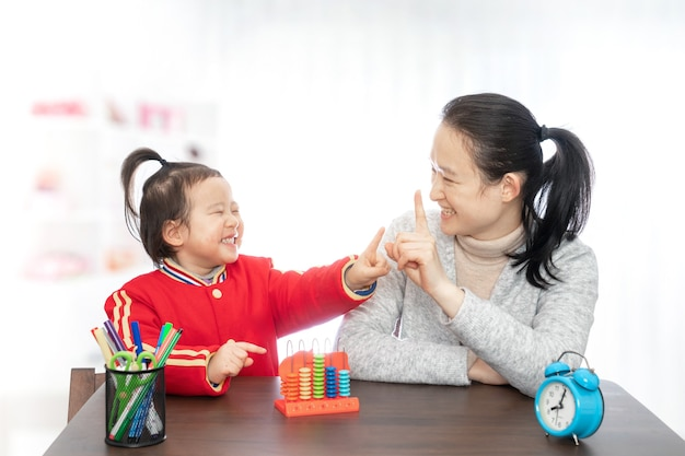 Young mother teaches her daughter to arithmetic