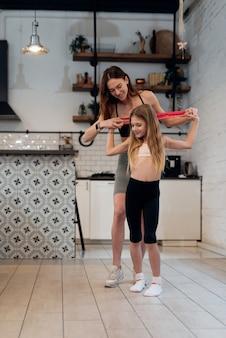 若い母親は娘に頭上の抵抗バンドストレッチの練習方法を教えています。