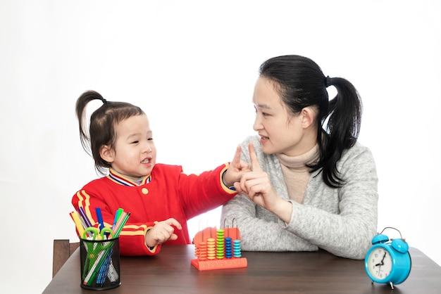 젊은 어머니가 딸에게 산술을 가르치고 있습니다.