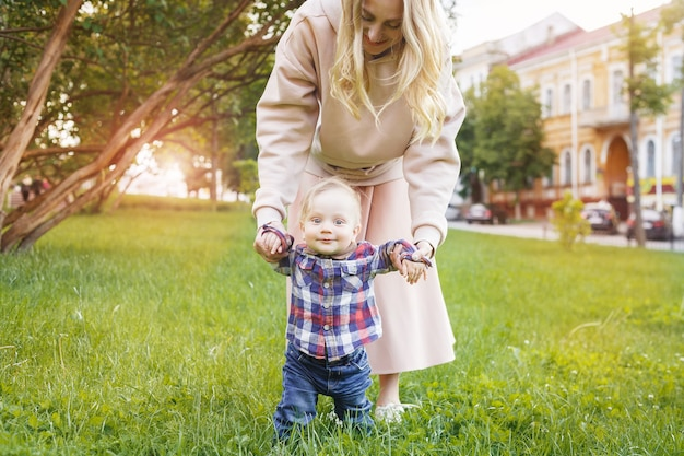 Young mother teaches her little son to walk on the grass in the park on a sunny day