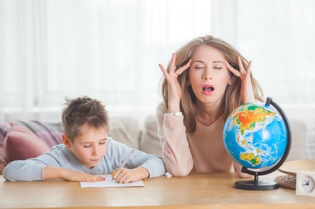 若い母親が幼い息子を自宅で教えています。ママと彼女の子供が屋内で地理を勉強