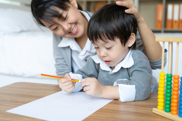 Young mother teaching her son write on paper with love