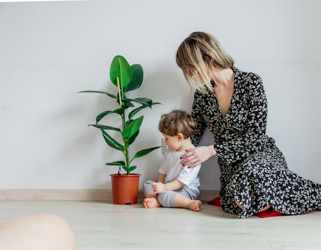 Young mother teaching a little toddler boy care with plant