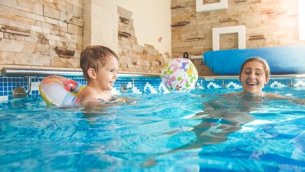 그녀의 작은 3 살 소년 아이 수영과 실내 수영장에서 화려한 비치 볼을 가지고 노는 젊은 어머니