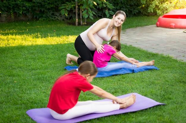 Молодая мать преподает йогу двух дочерей в парке