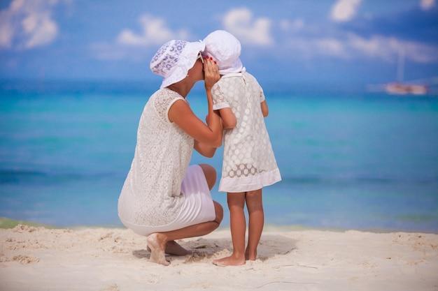彼女の小さな娘の耳に秘密を告げる若い母親 Premium写真
