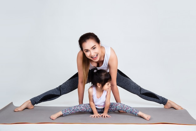 Young mother training lovely daughter with gymnastic