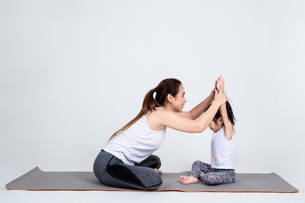 Young mother training lovely daughter with yoga