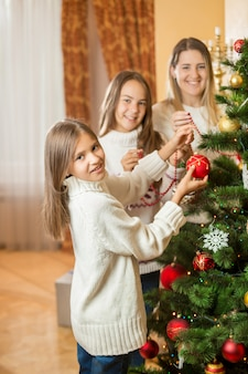 Young mother and two daughters decorating christmas tree with baubles