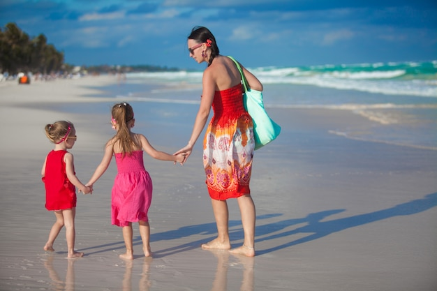 Young mother and two her fashion daughters walking at exotic beach on sunny day