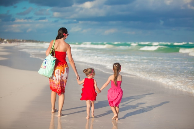 Young mother and two her fashion kids at exotic beach on sunny day