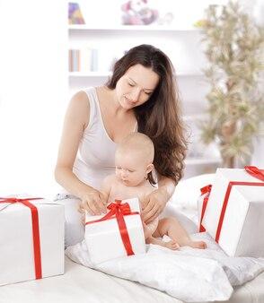 젊은 어머니는 선물 상자에 리본을 풀어줍니다.휴일 개념