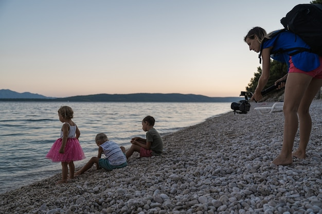 Young mother using a gimbal holder to video shoot her three kids playing at dusk on pebble beach by the sea.