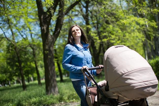 公園を歩いてベビーカーを押す若い母親