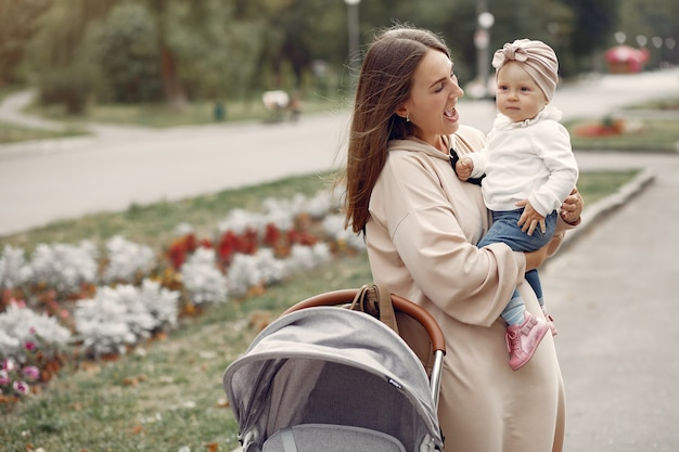 Young mother walking in a autumn park with carriage